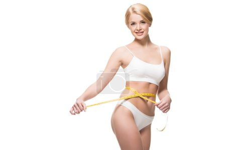 beautiful slim girl in white underwear holding measuring tape around waist and smiling at camera isolated on white