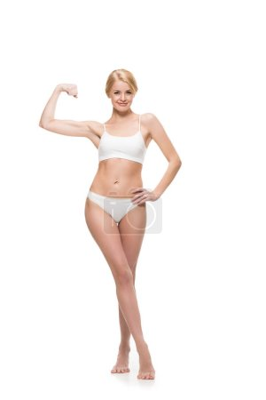 smiling slim girl in underwear standing with hand on waist and showing biceps isolated on white