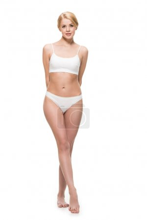 full length view of beautiful slim girl in underwear standing and looking at camera isolated on white