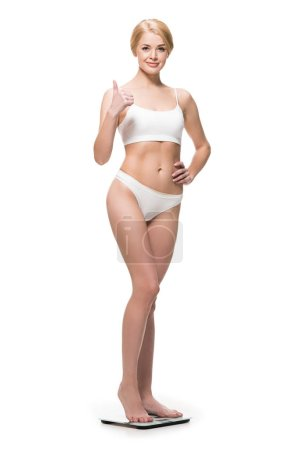 attractive happy slim girl in underwear standing on scales and showing thumb up isolated on white