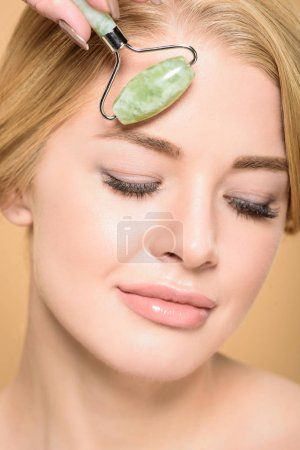 Photo for Beautiful smiling woman massaging face with jade roller isolated on beige - Royalty Free Image