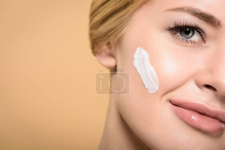 Photo for Cropped shot of attractive young woman with cosmetic cream on face smiling at camera isolated on beige - Royalty Free Image