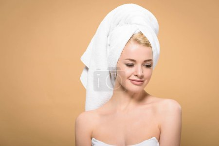 beautiful smiling young woman with towel on head looking down isolated on beige