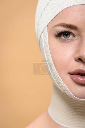 Photo pour La moitié de visage de jeune femme avec des bandages en regardant plus tête caméra isolée sur beige - image libre de droit