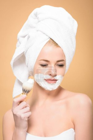 Photo for Woman with towel on head and shaving cream on face holding shaving brush and looking down isolated on beige - Royalty Free Image