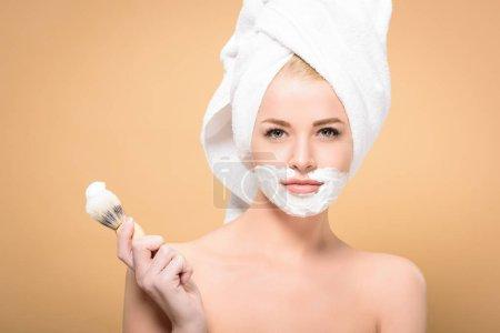 Photo pour Femme nue avec une serviette sur la tête et de la crème à raser sur le visage tenant blaireau et en regardant la caméra isolée sur beige - image libre de droit