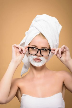 Photo for Beautiful girl with towel on head and shaving cream on face adjusting eyeglasses and looking away isolated on beige - Royalty Free Image