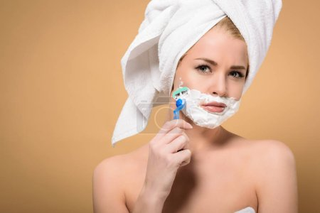 Photo for Young woman with towel on head shaving face with razor and looking at camera isolated on beige - Royalty Free Image