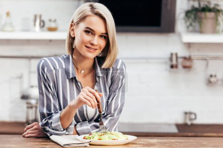 selective focus of attractive woman eating lunch and looking at camera