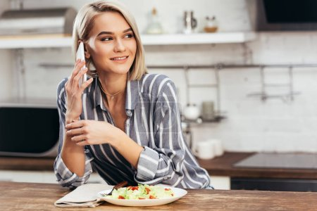 Photo for Selective focus of attractive woman eating and using smartphone - Royalty Free Image