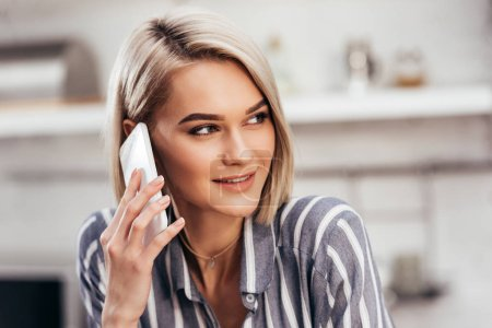 selective focus of attractive woman talking on smartphone