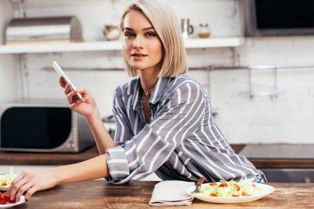enfoque selectivo de mujer atractiva sosteniendo el teléfono inteligente y mirando a la cámara