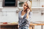Attractive woman using smartphone near table on kitchen