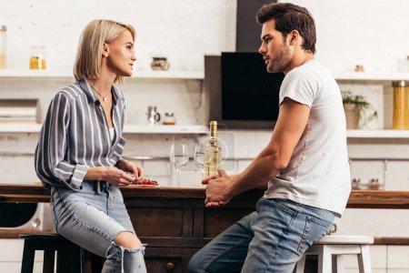 Foto de Atractiva novia hablando con novio guapo en cocina - Imagen libre de derechos