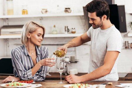 Photo pour Beau petit ami verser vin pour séduisante petite amie dans la cuisine - image libre de droit