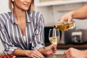 cropped view of of boyfriend pouring wine for attractive girlfriend