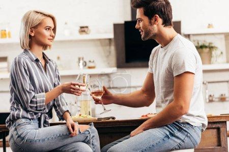 Photo pour Beau petit ami et séduisante petite amie tenant des verres à vin - image libre de droit