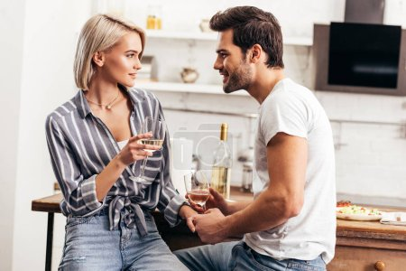 Photo pour Beau copain et copine tenant les mains et les verres à vin - image libre de droit