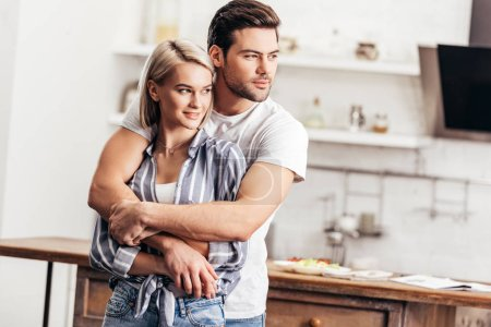 Photo for Handsome boyfriend and attractive girlfriend hugging in kitchen - Royalty Free Image