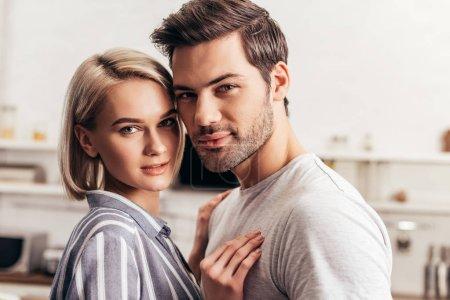 Foto de Selective focus of handsome boyfriend and attractive girlfriend hugging and looking at camera - Imagen libre de derechos