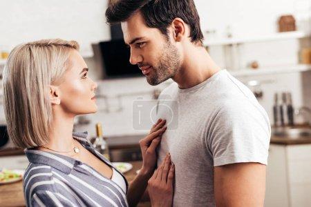 Photo pour Mise au point sélective de beau copain et séduisante copine debout dans la cuisine - image libre de droit