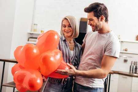 Photo for Handsome boyfriend greeting attractive girlfriend on Valentines day - Royalty Free Image