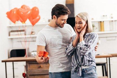 Foto de Selective focus of handsome boyfriend giving gift to attractive surprised girlfriend on Valentines day - Imagen libre de derechos