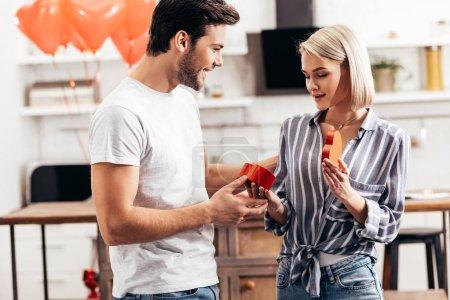 Foto de Enfoque selectivo del guapo novio regalar a atractiva novia dia de San Valentin - Imagen libre de derechos