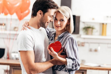 selective focus of handsome boyfriend giving gift to attractive girlfriend on Valentine's day