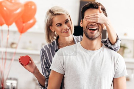 Photo for Selective focus of attractive girlfriend hugging and giving gift to handsome boyfriend on Valentines day - Royalty Free Image