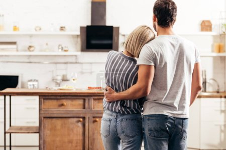 Photo for Selective focus of boyfriend and girlfriend hugging and standing in kitchen - Royalty Free Image