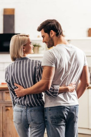 Photo for Selective focus of handsome boyfriend and attractive girlfriend hugging and standing in kitchen - Royalty Free Image