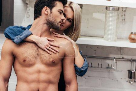 Photo pour Foyer sélectif de jeune couple étreignant à la cuisine - image libre de droit