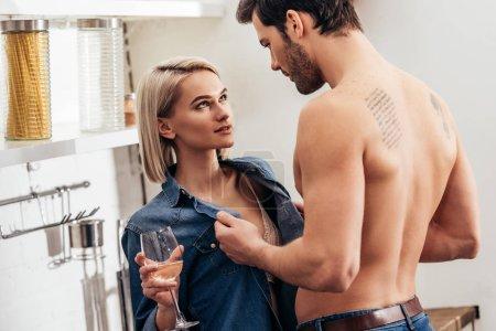 Photo pour Mise au point sélective de la séduisante copine et copain beau tenir le verre de vin et des caresses à la cuisine - image libre de droit