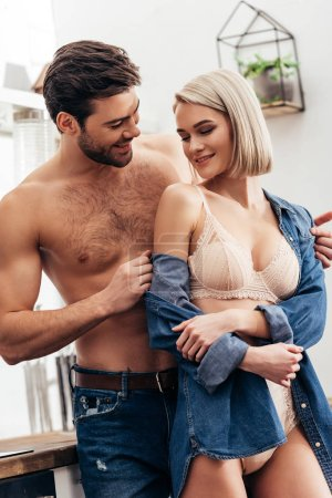 Photo for Selective focus of attractive girlfriend and handsome boyfriend hugging and smiling at kitchen - Royalty Free Image