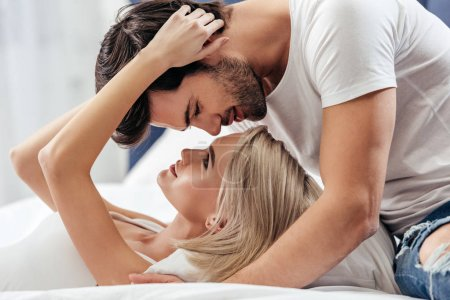 Photo pour Séduisante petite amie et beau copain baiser dans son lit - image libre de droit
