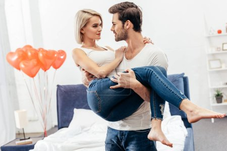 Photo for Selective focus of handsome boyfriend holding attractive girlfriend at bedroom on Valentines day - Royalty Free Image