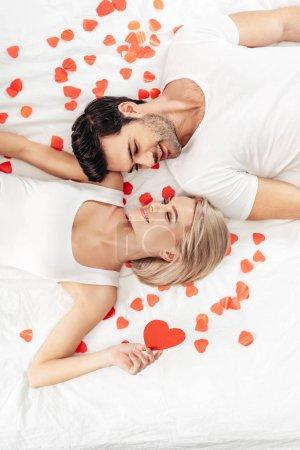Photo pour Vue de dessus de la petite amie attrayante et beau petit ami souriant et posant près des signes de coeur le jour de la Saint-Valentin - image libre de droit