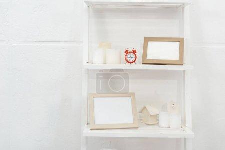 Photo pour Étagères avec horloge rouge, des cadres en bois et des bougies sur fond blanc - image libre de droit