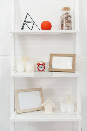Photo pour Shelves with red clock, wooden frameworks, bottle with seashells and candles on white background - image libre de droit