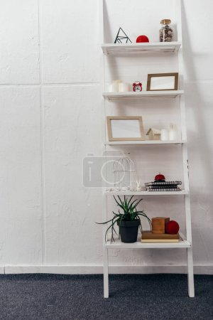 Photo for Shelves with red clock, wooden frameworks, plant, books, bottle with seashells and candles on white background - Royalty Free Image
