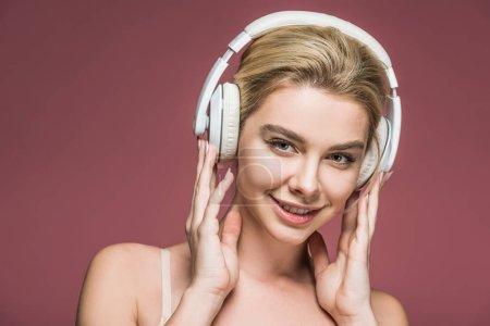 Photo pour Belle fille souriante écoutant de la musique avec écouteurs, isolé sur rose - image libre de droit