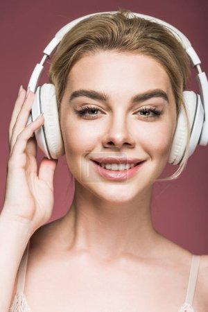Photo pour Femme attrayante écouter de la musique avec écouteurs, isolé sur rose - image libre de droit