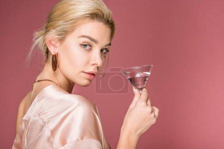 Foto de Hermosa chica elegante en traje de seda con Copa de cóctel, aislado en rosa - Imagen libre de derechos