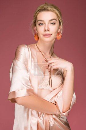 Photo for Elegant young woman posing in accessories, bra and silk robe, isolated on pink - Royalty Free Image