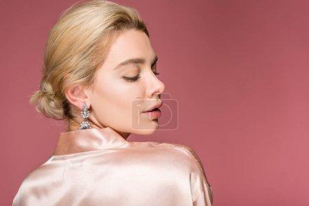 Photo pour Belle femme blonde posant dans boucles d'oreilles et robe de soie, isolé sur Rose - image libre de droit