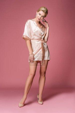 Photo pour Attrayant élégant femme posant en robe de soie sur rose - image libre de droit