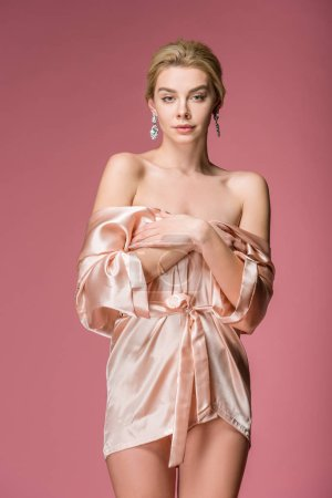 Foto de Elegante atractiva mujer posando en traje de seda, aislado en rosa - Imagen libre de derechos