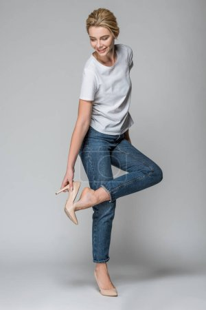 Photo for Attractive smiling woman in jeans wearing high heels, on grey - Royalty Free Image