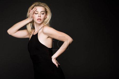 Photo pour Femme sexy en robe noire posant isolés sur noir - image libre de droit